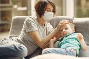mother checking her son for fever while wearing a face mask